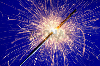 sparkler against blue background.