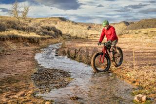 riding a fat bike across a stream