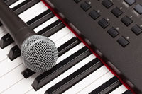 Microphone Laying on Electronic Synthesizer Keyboard Abstract