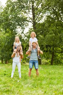 Kinder reiten auf dem Rücken ihrer Eltern