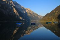 Summer morning at lake Klontalersee. Mountain range Glarnisch reflecting in the water.