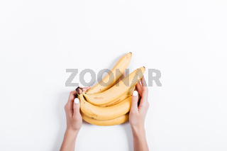 Female hand holding a bunch of bananas on a white table