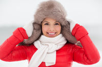 happy smiling woman in winter fur hat outdoors