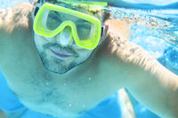 Man with snorkel mask underwater in swimming pool