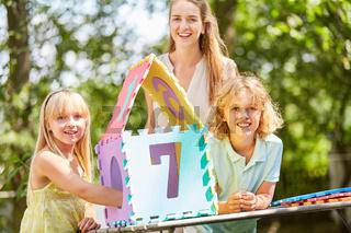 Mutter und Kinder bauen ein Eigenheim Puzzle