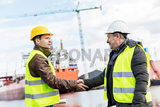 Business handshake in a shipyard. Shipbuilding industry