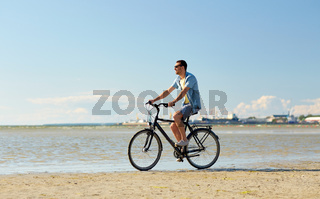 happy man riding bicycle along summer beach