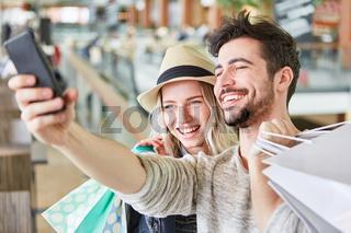 Junges Paar macht beim Shopping ein Selfie