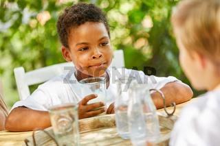 Afrikanischer Junge trinkt ein Glas Milch