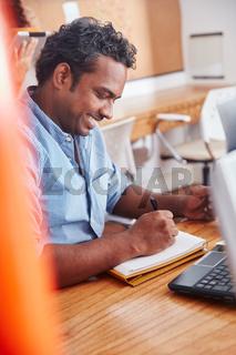 Indischer Mann macht sich Notizen