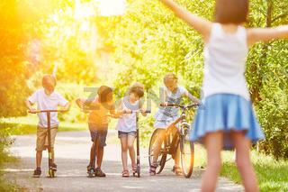Kinder machen Wettrennen mit Fahrrad und Roller