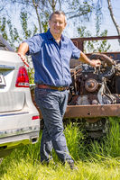 Man stands in front of old scrap car