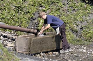 Zehnjähriger Junge beim Wandern erfrischt sich an einem Brunnen, Söllereck, Allgäuer Alpen, Bayern, Deutschland, Europa