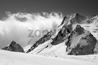 Black and white view on snowy sunlight mountains in clouds