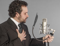 portrait of young man in suit singing with the studio microphone. Isolated on grey background. Singer concept.