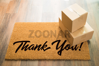Thank You Welcome Mat On Wood Floor With Shipment of Boxes