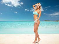 happy woman in bikini swimsuit on summer beach