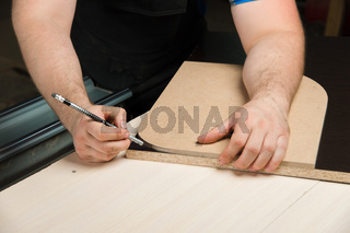 Male hands draw a pencil on the ruler