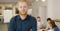 Man posing in office with coworkers