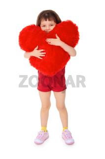 Little girl hugging a toy heart on a white