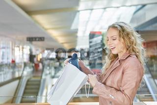 Frau blickt überrascht in eine Einkaufstüte