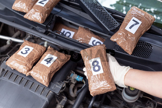 Policeman holding drug package found in engine compartment of a car