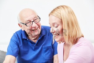 Senior und Tochter im Gespräch zu Hause