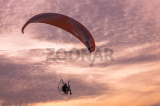 Paraglider flying over the beach at dusk