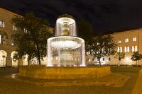 Beleuchteter Brunnen am Geschwister-Scholl-Platz in München