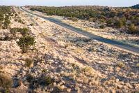 A modern asphalt road across Namibian endless savanna