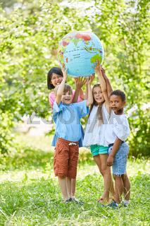 Multikulturelle Gruppe Kinder hält Weltkugel