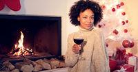 Pretty woman holds wine glass beside fireplace