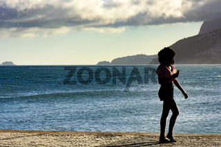 Girl walking in frot de sea with phone