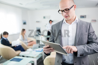 Geschäftsmann tippt auf Touchscreen seines Tablet