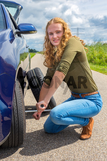 Dutch woman changing car tire on country road