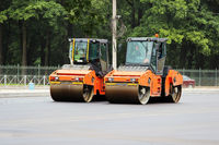 Two orange compactors make asphalt in the future parking lot for tourist buses. Gatchina.