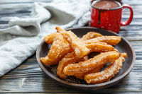 Dish with churros and hot chocolate.