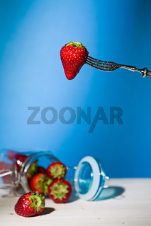 Strawberry suspended from a fork and under a jar of strawberries