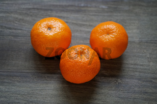 clementines or mandarin oranges on rustic wooden table