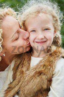 Mutter küsst liebevoll Tochter