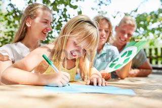 Familie und Mädchen beim Zeichnen