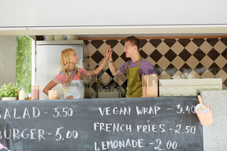 couple of sellers making high five at food truck