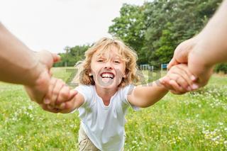 Blonder Junge tobt ausgelassen im Garten