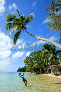 Young woman swinging on a rope swing at Pangaimotu island near Tongatapu island in Tonga