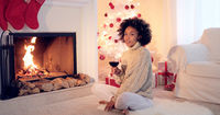 Woman in leggings and sweater sits by white tree