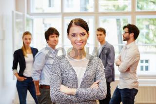 Geschäftsfrau steht zufrieden vor Business Team