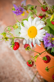 Ripe strawberries and a bouquet of forest flowers in a clay mug
