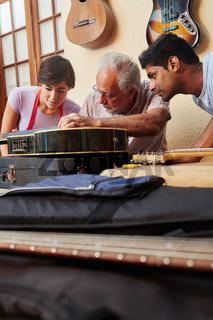 Gitarrenbauer und Lehrlinge reparieren Gitarre