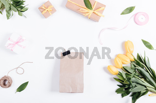 Gifts, tulips, ribbon, rope on a white table