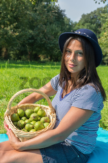 Portrait woman holds basket with pears in orchard